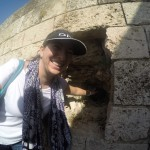 Caline touching a cannon ball in Byblos wall